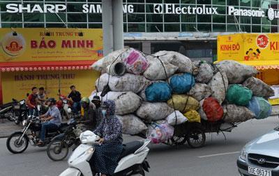 Hai người đàn ông đi xe máy kéo một lượng rác tái chế trên đường phố Hà Nội vào ngày 12 tháng 8 năm 2016.
