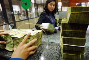 Nhân viên một Ngân hàng Thương mại ở Hà Nội đang nhận tiền gửi của khách hàng hôm 23/2/2011. AFP