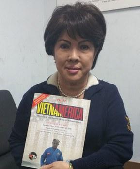 Nhà báo Triều Giang cùng poster quảng cáo phim VIETNAMERICA. Photo courtesy of Người Việt/Ngọc Lan.