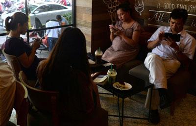 Người dân sử dụng điện thoại cầm tay, iPad lướt web trong một quán cà phê ở Hà Nội ngày 23 tháng bảy năm 2014.