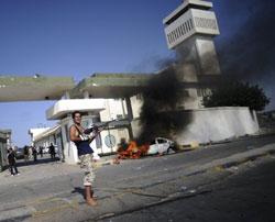 Khói bốc lên từ một chiếc xe cháy bên ngoài học viện quân sự của phụ nữ ở Tripoli vào ngày 22 tháng 8 năm 2011. AFP photo