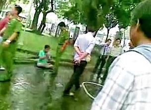 Công an đang giải tán các học viên Pháp Luân Công tại công viên Lê Văn Tám/TPHCM vào ngày 9 tháng 10, 2011.