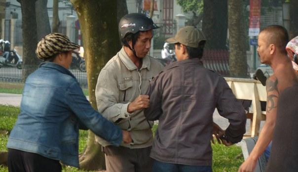 Một tín đồ Pháp Luân Công Việt Nam (đội mũ bảo hiểm) bị ba cảnh sát mặc thường phục trấn áp trước tòa đại sứ Trung Quốc tại Hà Nội vào ngày 24 tháng 11 năm 2011.