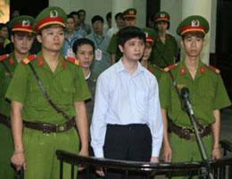 Anh Vũ Đức Trung (giữa, hàng đầu) và anh Lê Văn Thành (giữa, sau anh Trung), hai học viên Pháp Luân Công tại Tòa án nhân dân Hà Nội sáng 10/11/2011.AFP