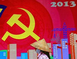 Một ngươi phụ nữ  đi ngang qua một biểu ngữ của đảng cộng sản VN. AFP