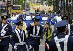 Cảnh sát kiểm soát một cuộc diễu hành bởi hàng trăm người ủng hộ Pháp Luân Công tại Bắc Kinh hôm 25/4/2008, một ngày trước sự kiện rước đuốc Olympic. AFP