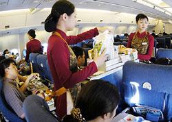 Các tiếp viên hàng không đang phục vụ bữa ăn cho khách. Photo courtesy of yeudulich.vn
