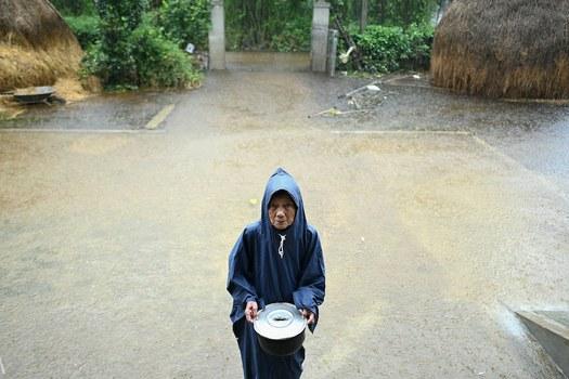 Hình minh hoạ. Một phụ nữ lớn tuổi cầm bát cơm cạnh căn nhà ngập nước của bà ở Hải Lăng, tỉnh Quảng Trị hôm 16/10/2020