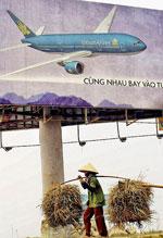 Một nông dân gánh rơm dưới một áp phích quảng cáo của những máy bay Boeing 777 mà hãng hàng không Việt Nam gần đây đã mua hàng tỷ đô la. AFP