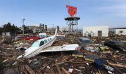 Những mảnh vụn của một chiếc máy bay tư nhân và xe hơi ở bên ngoài phi trường Sendai hôm 13/03/2011. AFP Photo