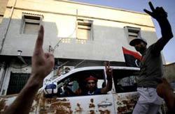 Quân nổi dậy Libya làm dấu chiến thắng khi họ tuần tra trên đường phố thủ đô Tripoli ngày 22 tháng 8 năm 2011. AFP photo