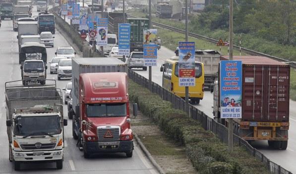 Xe tải và container di chuyển trên Quốc lộ 5 ở Hà Nội nối với cảng Hải Phòng.