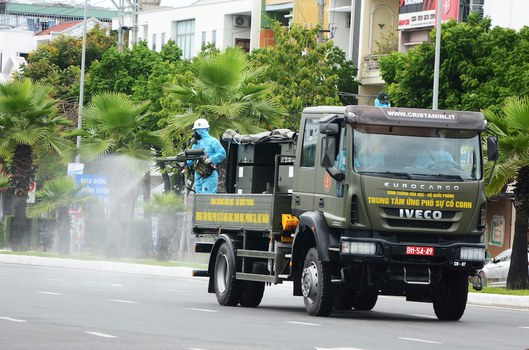 Hình minh hoạ. Một người lính phun thuốc khử trùng từ xe của quân đội trên đường phố Đà Nẵng hôm 3/8/2020