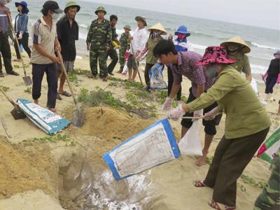 Dân làng chôn cá chết trên một bãi biển ở Quảng Bình, Việt Nam hôm 28/4/2016.