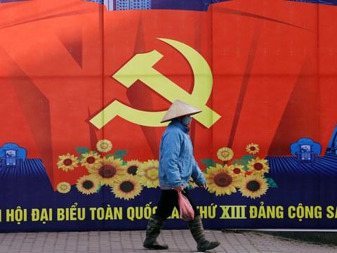 Hình minh hoạ. Một người phụ nữ đi qua tấm biển quảng bá cho Đại hội 13 ở Hà Nội hôm 18/1/2021