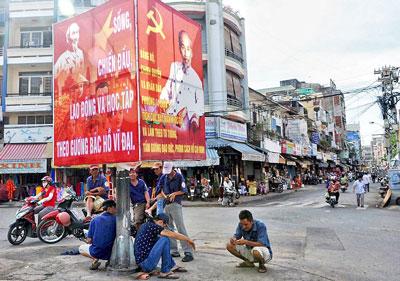 Ảnh chụp tháng 11 năm 2013 cho thấy những người dân thất nghiệp ngồi chờ dưới chân dung ông Hồ Chí Minh hàng ngày ở các ngã ba ngã tư đường xem có ai mướn làm bất cứ công việc gì theo giờ theo ngày...(AFP)