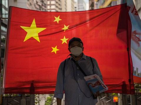 Hình minh hoạ: Một người ủng hộ chính phủ Trung Quốc phát báo trước là cờ Trung Quốc ở Hong Kong hôm 1/7/2020.