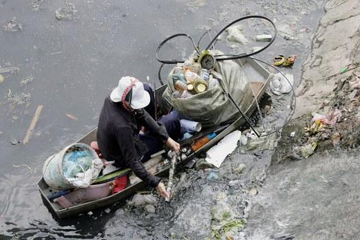 Hình minh họa. Người vớt rác trên một con sông ô nhiễm ở Hà nội hôm 20/10/2006