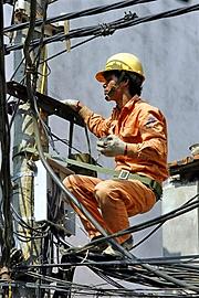 Kiểm tra đường giây trên cột điện. AFP