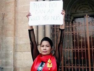 """Bà Minh Hằng với biễu ngữ: """"Phản đối đàn áp người ủng hộ Quốc hội ra luật biểu tình"""", trước khi bị bắt. Source danlambao"""