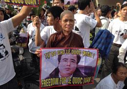 Một nữ tu Phật giáo cầm biểu ngữ kêu gọi trả tự do cho luật sư Lê Quốc Quân, cùng hàng trăm người cố gắng đến gần Toà án nơi LS Lê Quốc Quân bị đưa ra xét xử  ngày 02 tháng 10 , năm 2013. AFP