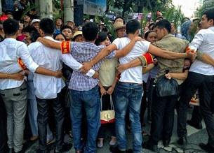 An ninh, công an thường phục làm hàng rào ngăn chặn những người muốn đến dự phiên tòa công khai xét xử LS Lê Quốc Quân