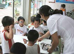 Trong giờ ăn ở trường  mầm non công lập, mỗi cô giáo phải chăm chừng 20-30 cháu. Photo: Tiến Dũng.