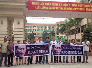 Gia đình blogger Điếu Cày cùng bạn bè căng biểu ngữ trước cổng Tổng cục 8 đòi trả tự do cho ông sáng ngày 26/07/2013.