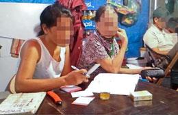 """Một cụ bà ngoài 70 tuổi (phải) đọc số lô đề để """"thư ký"""" vào bảng -Photo Ha An/TN"""