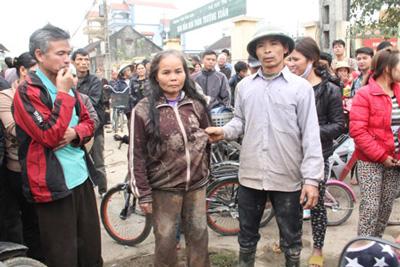 Bà Lê Thị Thoa mặc nguyên bộ quần áo bê bết bùn do bị công an xô ngã dúi dụi xuống ruộng lên hội trường thôn phản đối (ảnh báo danviet.vn)