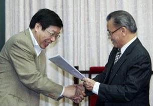 Nguyên Bộ trưởng Nguyễn Đình Lộc (phải) trao bản kiến nghị sửa đổi Hiến pháp cho Phó Chủ nhiệm Ủy ban Pháp luật Lê Minh Thông.