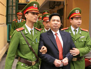 Công an dẫn giải Tiến sĩ Cù Huy Hà Vũ rời toà. AFP