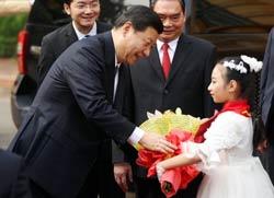 PCT Trung Quốc Tập Cận Bình (T) nhận hoa từ một bé gái VN trong chuyến thăm Hà Nội hôm 21/12/2011. AFP photo