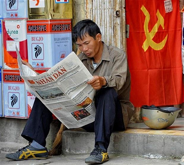 Một công nhân đang đọc báo đảng bên canh cờ đảng ở Hà Nội
