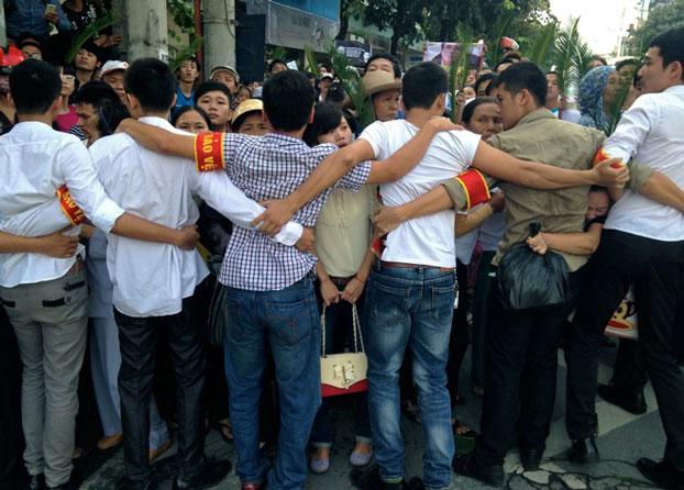 Công an, an ninh, ngăn chặn những người ủng hộ LS Lê Quốc Quân đến gần Tòa án Nhân dân thành phố Hà Nội nơi xét xử Luật sư Lê Quốc Quân với cáo buộc Trốn thuế hôm 2/10/2013. AFP PHOTO/Cat BARTON.