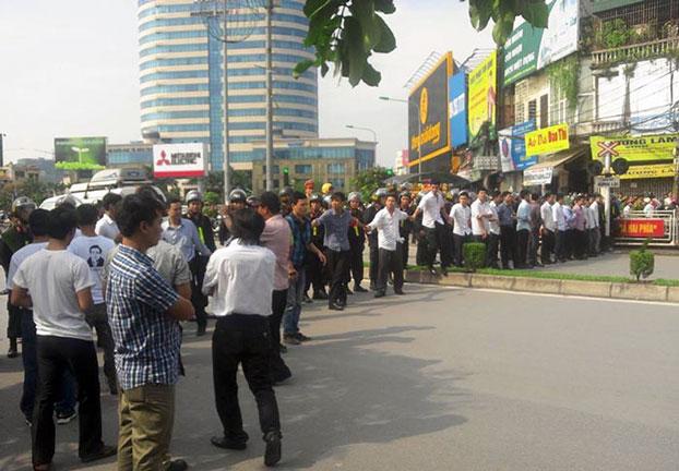 """Công an, an ninh, CSCĐ ngăn chặn những người ủng hộ LS Lê Quốc Quân đến gần Tòa án Nhân dân thành phố Hà Nội nơi xét xử Luật sư Lê Quốc Quân với cáo buộc """"Trốn thuế"""" hôm 2/10/2013. Photo courtesy of VRNs."""