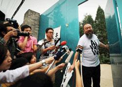 Nghệ sĩ Ngải Vị Vị trả lời các phóng  viên báo chí tụ tập trước nhà. AFP