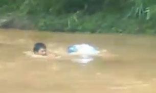 Hình ảnh chụp từ video clip: cô giáo chui túi nilon vượt suối lũ đến trường.