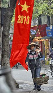 Một người bán hàng rong trên đường phố Hà Nội. AFP