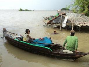 Nhiều trẻ em xã Tân Công bơi xuồng cùng ba mẹ kiếm cá. Source tienphong-online