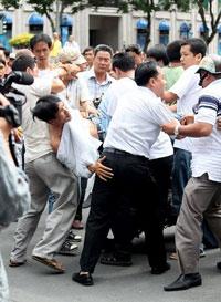 Một người đàn ông bị công an mặc thường phục bắt trong lúc đang tuần hành phản đối Trung Quốc xâm phạm lãnh hải Việt Nam. Photo by Quang Dư