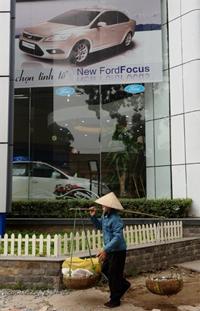 Người lao động nghèo ngang một cửa hàng trưng bày xe hơi ở Hà Nội tháng 2/2009. AFP photo