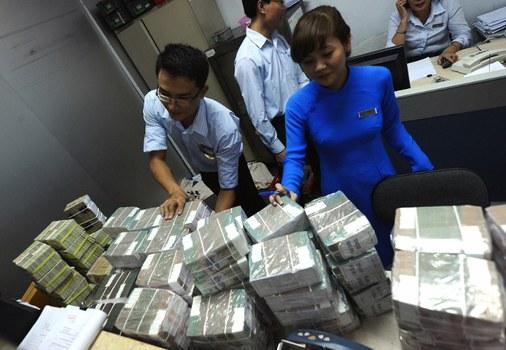 Nhân viên Ngân hàng TMCP Á Châu (ACB) tại Hà Nội kiểm tra tiền đồng Việt Nam. Ảnh minh họa chụp trước đây.