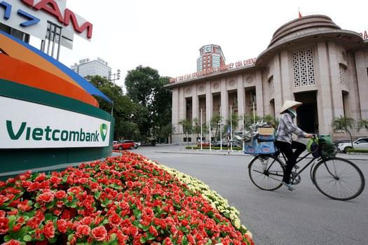 Hình minh hoạ. Một người dân đi xe qua trụ sở của ngân hàng Vietcombank ở Hà Nội