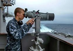 Một lính hải quân Hoa Kỳ nhìn qua kính viễn vọng trên tàu USS George Washington tại biển đông hôm 24/10/2013. AFP photo