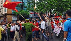 Công an ngăn cản những người biểu tình hô to khẩu hiệu chống Trung Quốc khi họ diễu hành về phía Đại sứ quán Trung Quốc tại Hà Nội vào ngày 01 tháng 7 năm 2012. AFP photo
