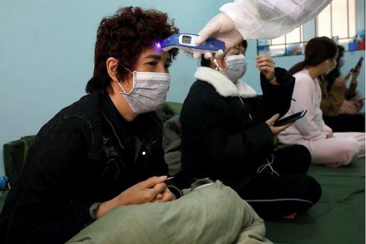 Hình minh hoạ. Bác sĩ quân đội kiểm tra thân nhiệt cho người về từ Trung Quốc đang được cách ly ở một trung tâm ở Lạng Sơn hôm 20/2/2020