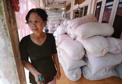 Nông dân Đặng Thị Bảy tồn trữ gạo tại nhà ở tỉnh Tiền Giang hôm 06/6/2010. AFP photo