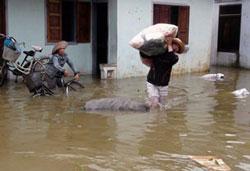 Người dân di chuyển đồ đạc từ một ngôi nhà bị ngập lụt trong thành phố Qui Nhơn, tỉnh Bình Định hôm 16/11/2013. AFP photo