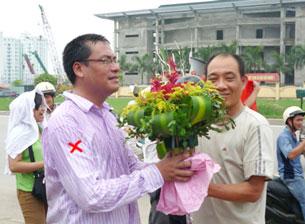 Anh Nguyễn Chí Đức (x), nạn nhân của cú đạp lịch sử, nhận hoa</br> từ người thân sau khi được công an thả hôm 17/7/2011. Hình do anh Đức gửi RFA